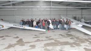 Eine Regenpause nutzen die Teilnehmer für ein Gruppenbild in der Halle, eingerahmt von zahlreichen Schleicher-Oldtimern.
